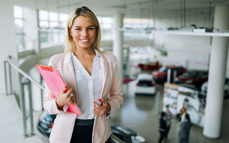 F&I Manager Hired at Auto Dealership Standing with Clipboard