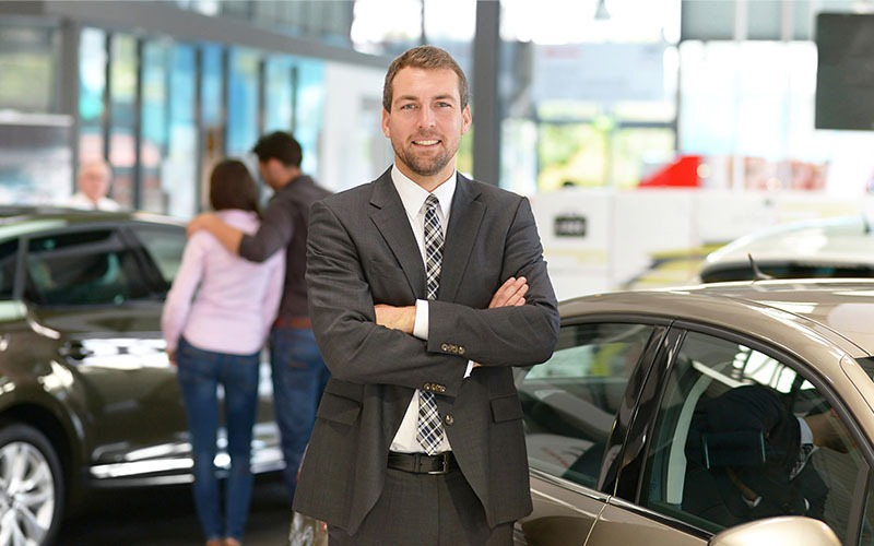 F&I Manager at Dealership Standing by Car