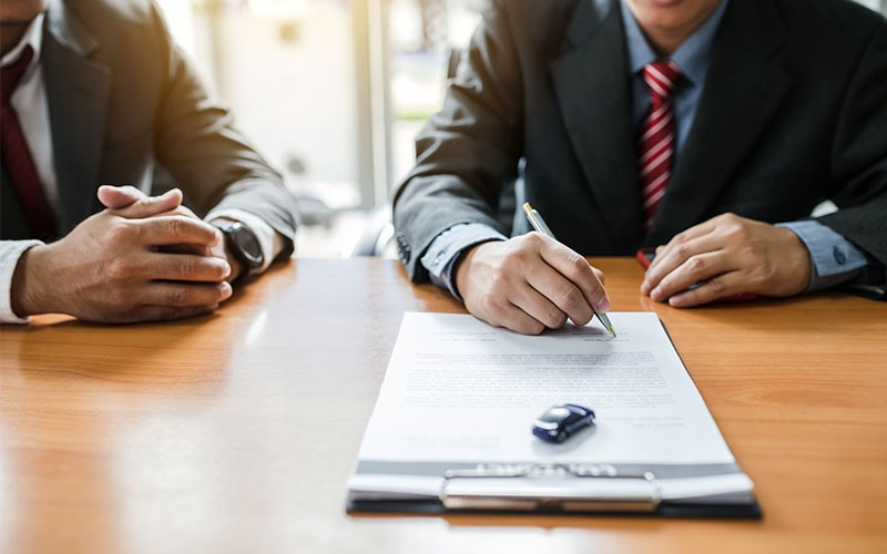 Auto Dealership Finance Manager With Customer Signing Contract